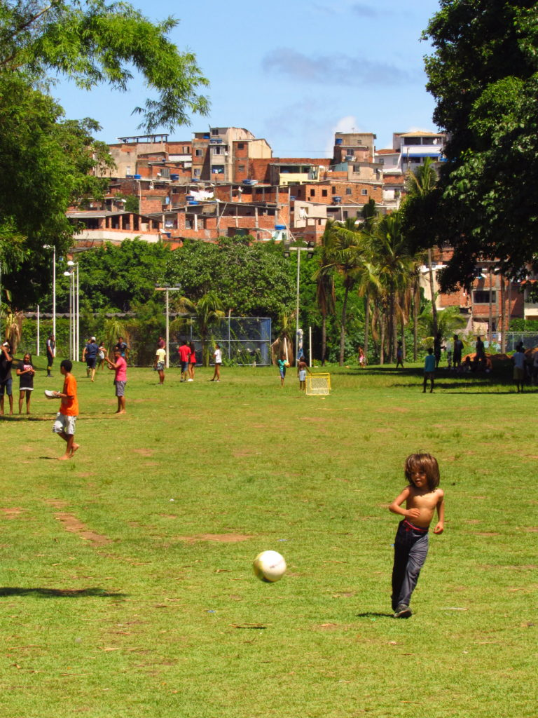 garoto jogando bola no parque da cidade