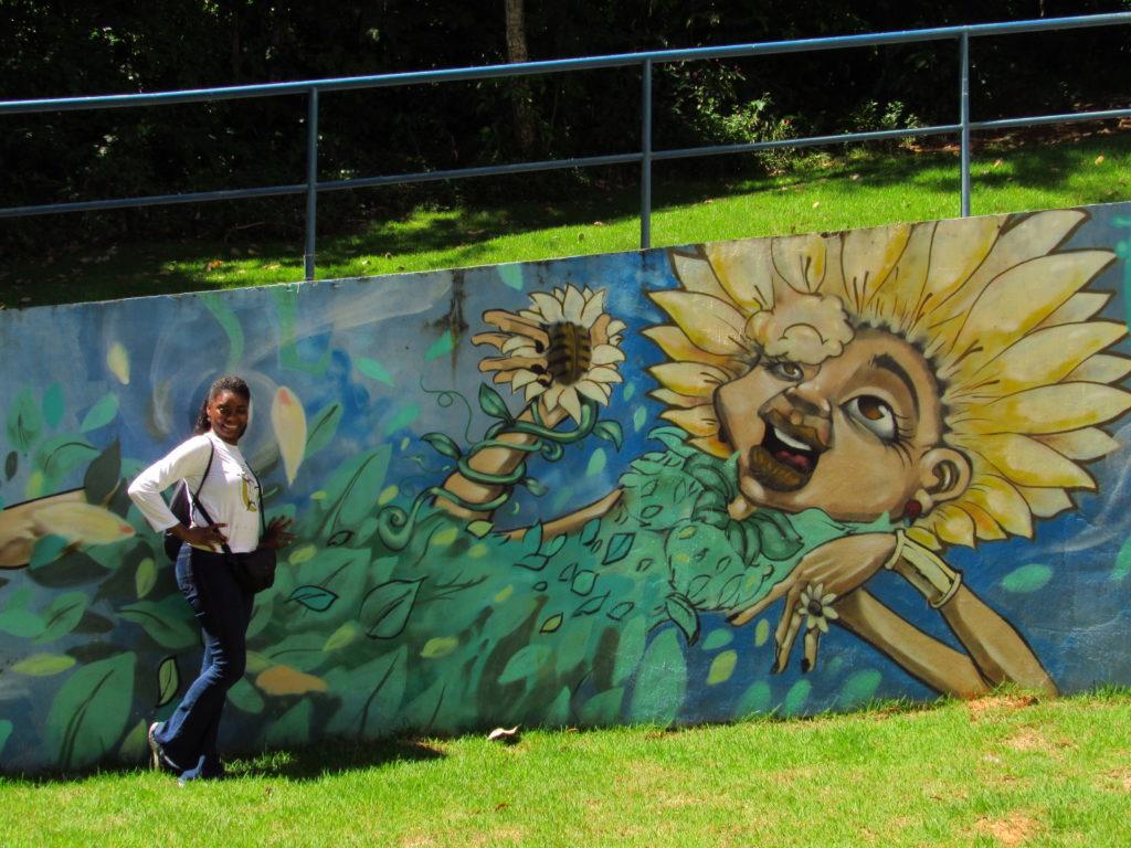uma pessoa posando ao lado de um grafite no parque da cidade salvador
