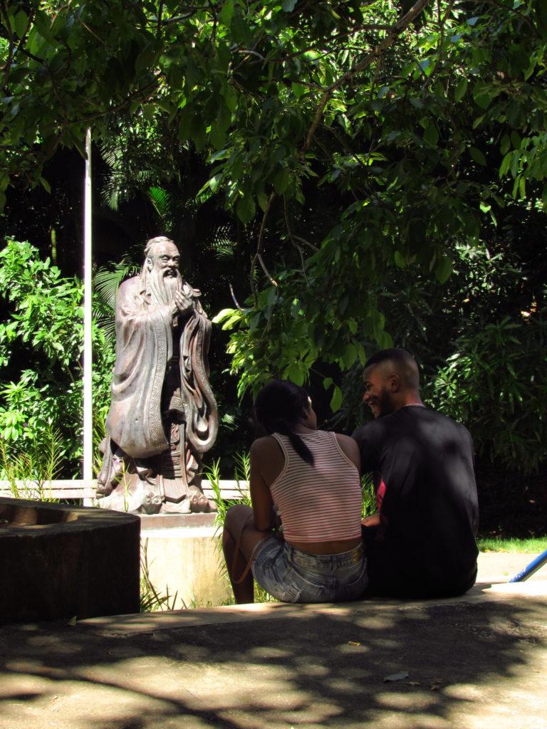 casal na frente da estatua de confucio no parque da cidade salvador